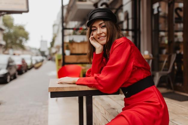 Meisje 23 jaar oud uit frankrijk poseren zittend in straatcafé. gezellig schot van elegante dame in rode jurk met wijde mouwen