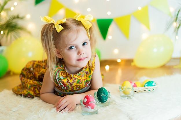 Meisje 3 jaar oud liggend op de vloer met heldere gele kleren met paaseieren