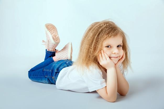 Meisje 4 jaar oud met krullend haar dat wit overhemd, op de vloer ligt, en jeans die, handen houdt kijkt die haar hoofd houden kijken