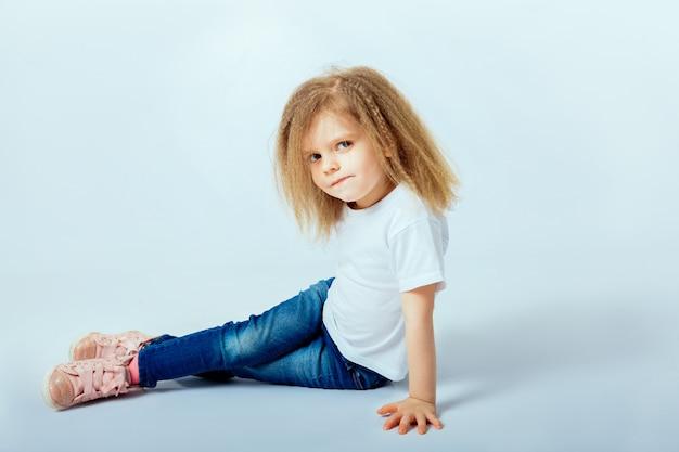 Meisje 4 jaar oud met krullend haar dragen wit shirt, spijkerbroek, roze laarzen zittend op de vloer, glimlachen en kijken