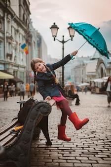 Meisje 6 jaar oud kind met een paraplu in rubberlaarzen die pret op een bank in het centrum van moskou in de herfst of de lente hebben.