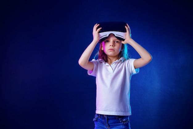 Meisje 7 jaar ervaart vr-headsetspel op kleurrijk. kind gebruikt een gaminggadget voor virtual reality. nam het op en vragend