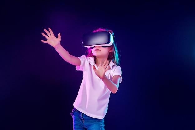 Meisje 7 jaar ervaart vr-headsetspel op kleurrijk. kind gebruikt een gaminggadget voor virtual reality.