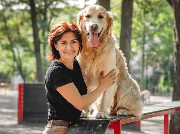 Meisje aaien golden retriever hond na training en glimlachend buitenshuis. jonge vrouw met hondje petportrait in het park samen