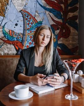 Meisje aan de bar aan een tafel met een telefoon in haar handen en een boek.