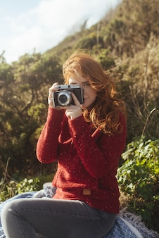 Meisje aan de kust met een vintage camera
