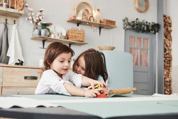 Meisje aan de rechterkant lacht en wil plezier hebben. twee kinderen spelen met geel en oranje speelgoed in de witte keuken.