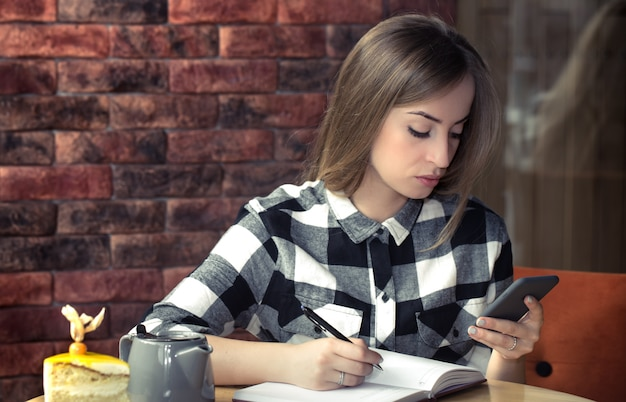 Meisje aan de tafel in het café met behulp van de mobiele telefoon en schrijven