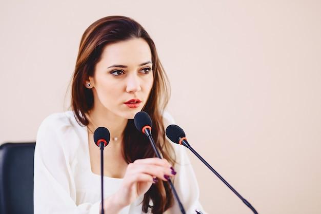 Meisje aan de tafel spreekt in microfoons in de conferentiezaal