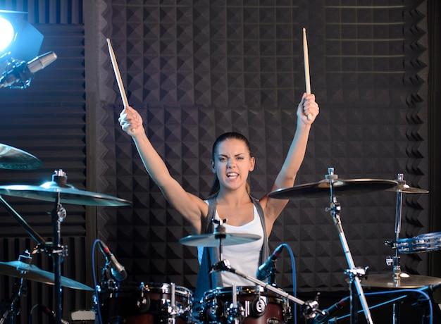Meisje achter drum-type installatie in een professionele studio.