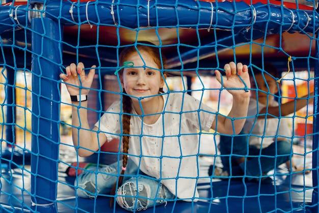 Meisje achter het raster in het speldoolhof in het entertainmentcentrum. vrouwelijk kind vrije tijd op vakantie, kindergeluk, gelukkig kind op speelplaats