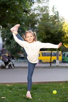 Meisje acrobaat in het park toont bindgaren