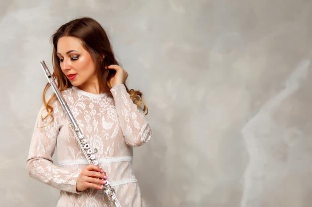 Meisje actrice in pak met fluit op lichte achtergrond met fluit in de hand