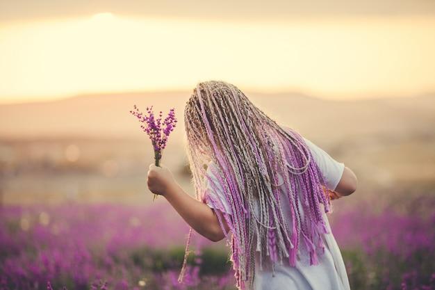 Meisje afgebeeld vanaf de achterkant met een boeket op een lavendelveld