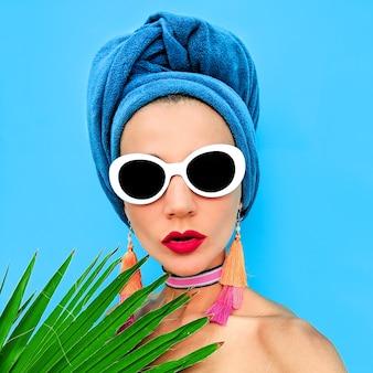 Meisje afrikaanse stijl met een hoofddoek, zonnebril en oorbellen. strandmodeconcept