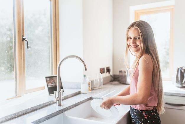 Meisje afwassen, eenvoudige huishoudelijke taken
