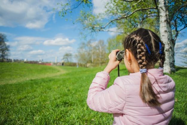 Meisje analyseert het park met haar verrekijker