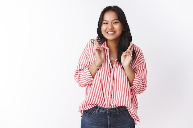 Meisje anticipeert met opwinding voor valentijnsdag kruis vingers voor geluk hoop datum gaat goed glimlachend opgewonden poseren hoopvol, bidden voor met uitkomen tegen witte muur