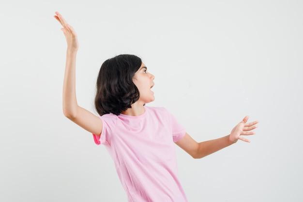 Meisje armen strekken, opzij kijken in roze t-shirt en nieuwsgierig, vooraanzicht kijken.