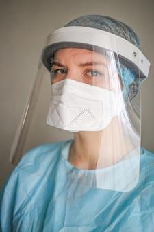 Meisje arts verpleegster in een beschermend pak en masker en beschermende bril