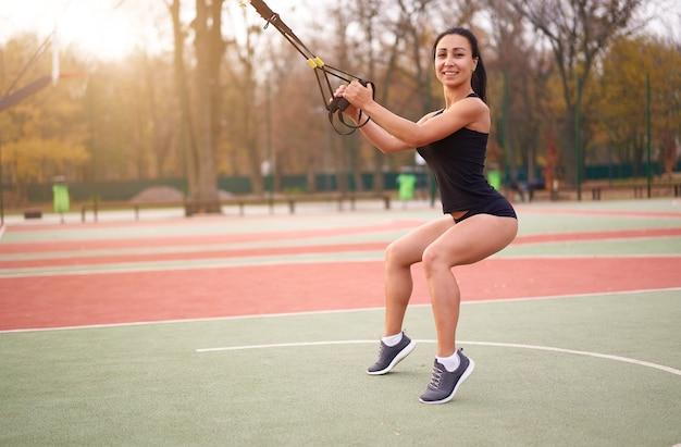 Meisje atleet training met behulp van trx op sportground. gemengd ras jonge volwassen vrouw training met ophangsysteem. gezonde levensstijl. buitenspeeltuin.