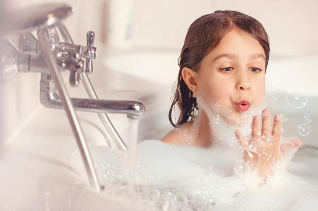 Meisje baadt en speelt met schuim in de badkamer.