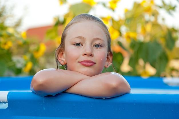 Meisje baadt in een blauw zwembad in een landhuis