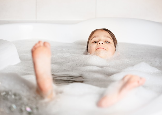 Meisje baden en spelen met schuim in de badkamer