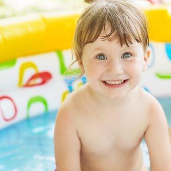 Meisje badend in een opblaasbaar zwembad