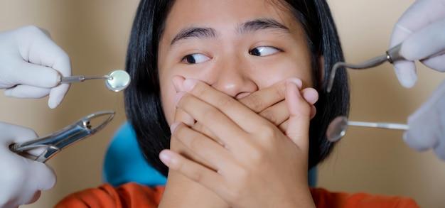Meisje bang door tandartsen bedekt haar mond in het kantoor van de tandarts