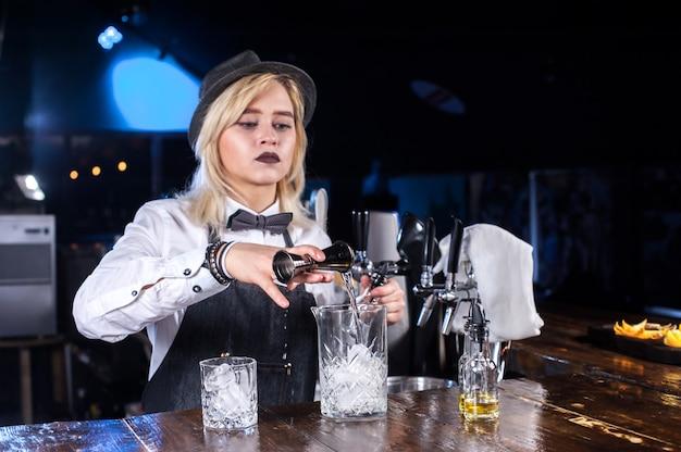 Meisje barman formuleert een cocktail achter de bar