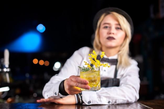 Meisje barmeisje formuleert een cocktail op de pothouse