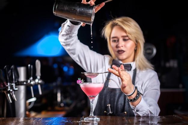 Meisje barmeisje formuleert een cocktail op het café