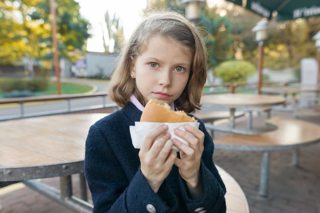 Meisje basisschool student eet hamburger, sandwich op een terras