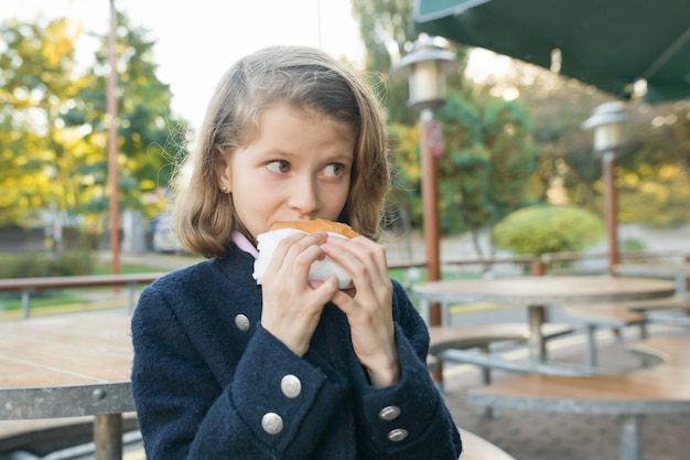 Meisje basisschool student eet hamburger, sandwich op een terrasje