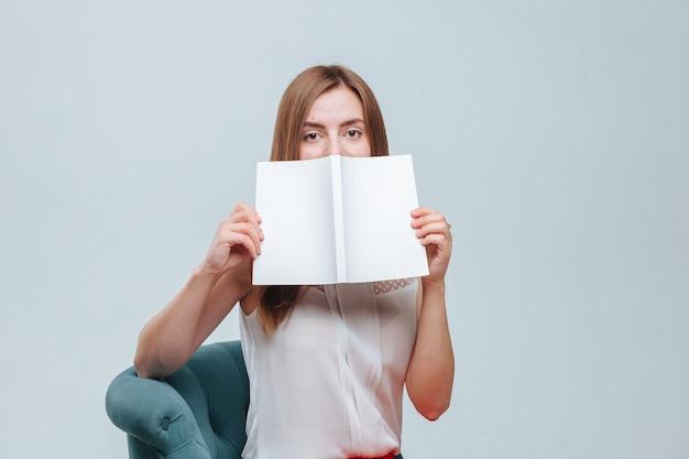 Meisje bedekt haar gezicht met een boek met een witte omslag