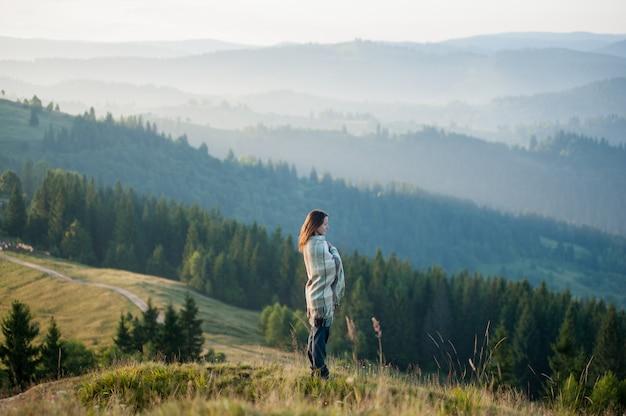 Meisje bedekt met deken staande op heuvel