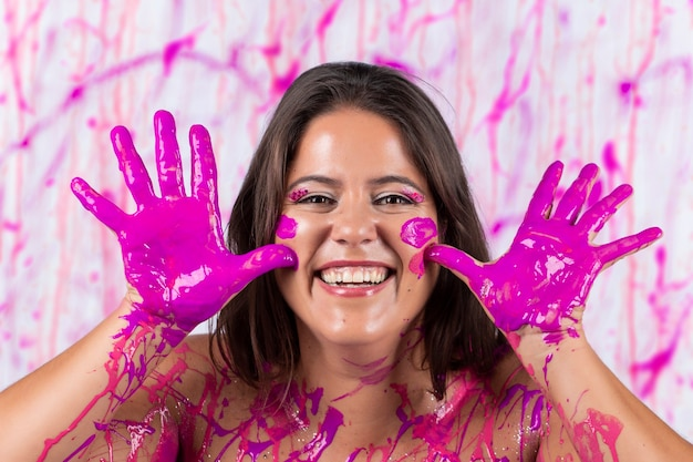 Meisje bedekt met roze verf met plezier en vrij zijn, op een concept dat helpt tegen het bewustzijn van borstkanker en de bevrijding van vrouwen.