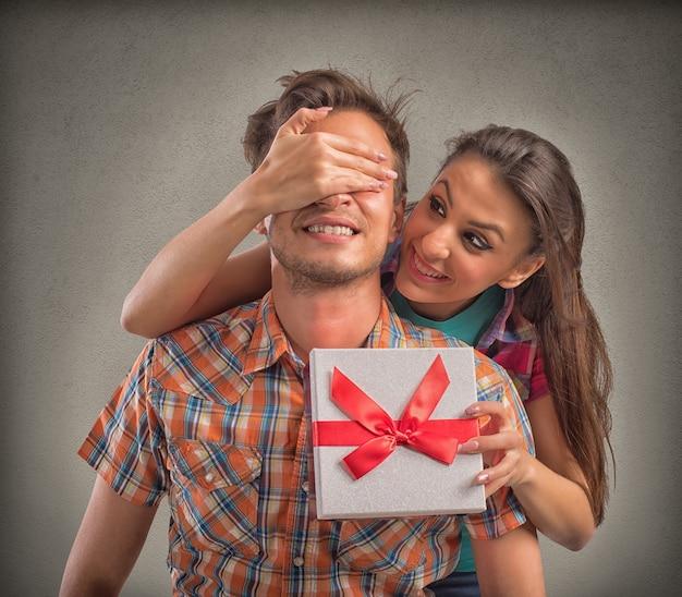 Meisje bedekt ogen jongen terwijl geeft hem een geschenkdoos