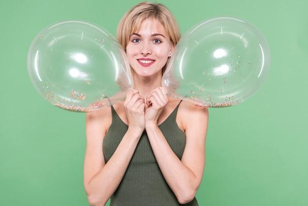 Meisje bedrijf ballonnen dicht bij haar gezicht