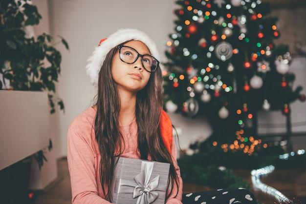 Meisje bedrijf geschenk en overweegt