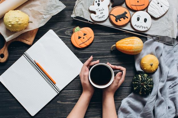 Meisje bedrijf kopje koffie, peperkoek voor halloween en schrijven op een notitieboekje.