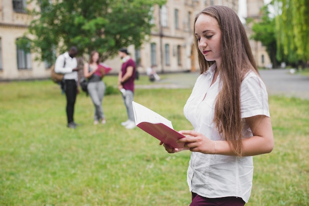 Meisje bedrijf notitieboekje lezen buiten staan