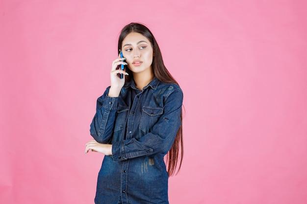 Meisje bedrijf praten met haar blauwe smartphone