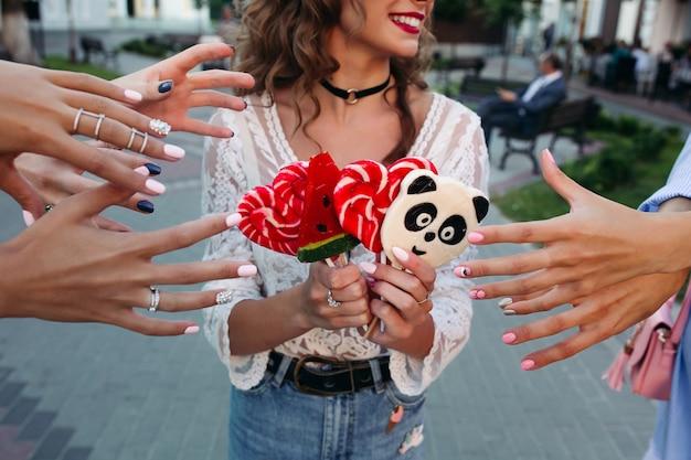 Meisje bedrijf snoepjes op stok en handen van drie meisjes handen uitrekken om snoep te nemen.