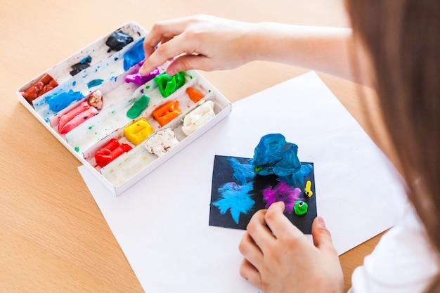 Meisje beeldhouwen uit plasticine, klei, deeg, diy thuis, creativiteit