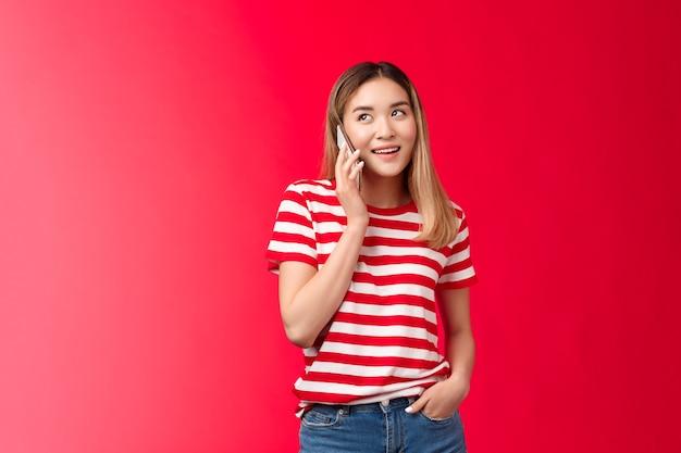 Meisje belt vriend en regelt vergadering leuke moderne aziatische vrouw houdt smartphone in de buurt van oor kijk weg sp...