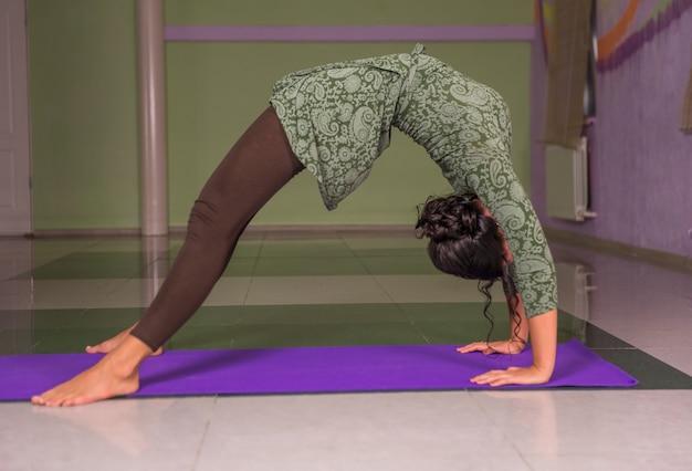 Meisje beoefenen van yoga-oefeningen in fitness klasse