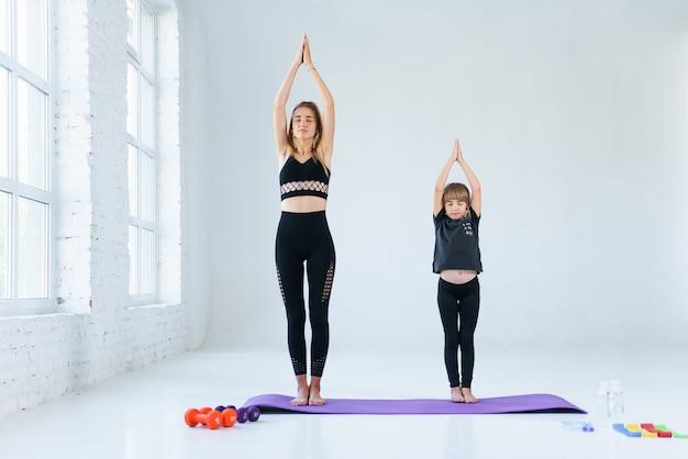 Meisje beoefenen van yoga, permanent in vrksasana oefening met namaste, boom pose. vrouwelijke meditatie op witte loft.