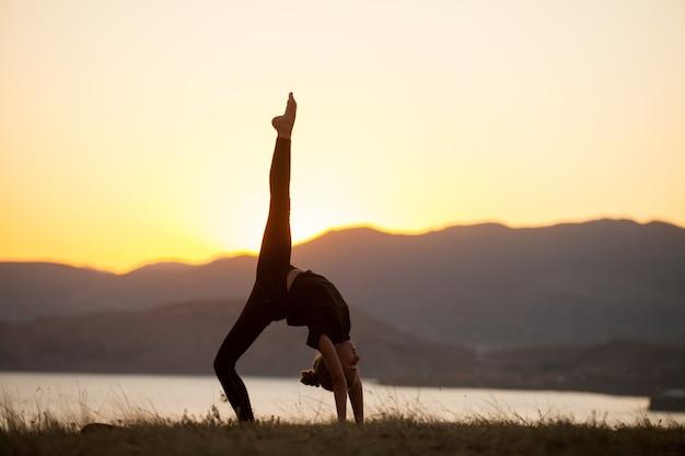 Meisje beoefent yoga in de bergen aan de oceaan.